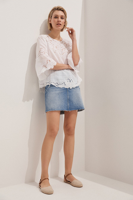 Woman wearing the Tia Embroidered Blouse and Alectrona Denim Skirt
