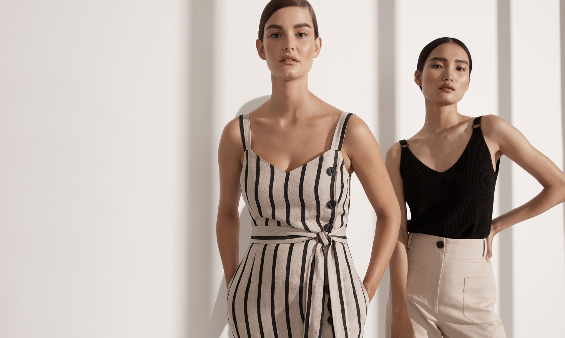 Woman on the left wearing the Button Linen Slip. Woman on the right wearing the Ring Trim Knit Tank and Urban Culottes