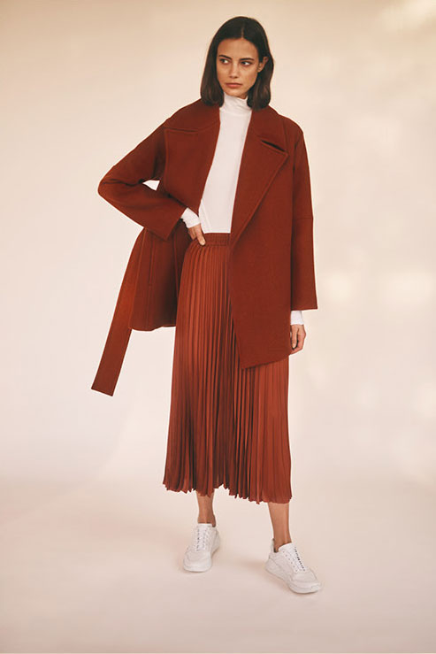 Woman wearing the Lapel Peacoat, Rib Turtle Neck, Pleated Twill Skirt and Skye Sneaker